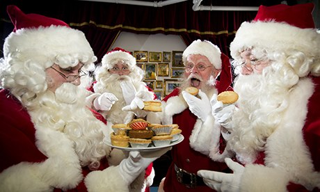 Mince pies being tasted by four Santa Claus at the Ministry of Fun, South East London.